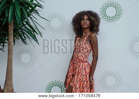 Attractive and slander afro american girl standing in a shopping mall in front of white wall.