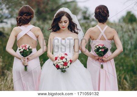 bride and bridesmaid in nature with bouquets of flowers