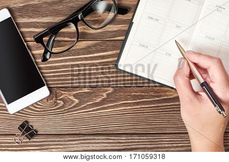 Woman Hand With A Pen Writting Blank Notebook