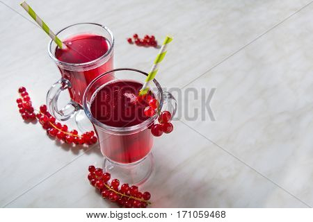 Two cup of red currant aerated lemonade with green straw with copy space