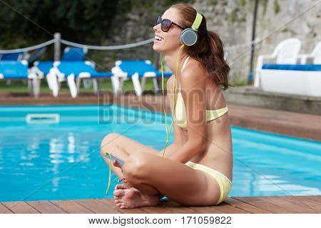 Sexy woman in the yellow bikini on the sun-tanned slim and shapely body is posing near the swimming pool