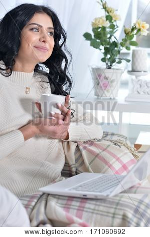 Young woman sitting in armchair using laptop and drinking tea