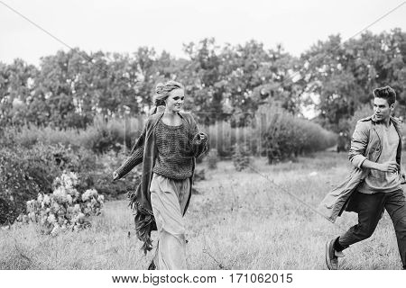 Young man and woman walking in a field. Love story. Fashion photography concept. Young man in trenchcoat girl in a sweater and a skirt.