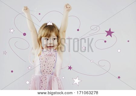 Cheerful little girl, with curly blond hair, wearing on pink dress and fairy wings, puts her hands up with magic stick, on gray background with painted purple and white stars and painted crown on her head, in studio, waist up