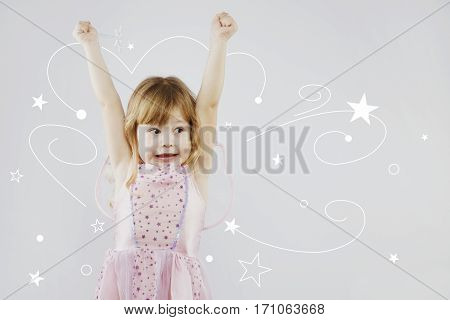 Cheerful little girl, with curly blond hair, wearing on pink dress and fairy wings, puts her hands up with magic stick, on gray background with painted white stars, in studio, waist up