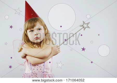 Upset girl, with curly blond hair, wearing on pink dress, red festal hat and fairy wings on her back, posing with silver magic stick, on gray background with white and purple stars, in studio, waist up