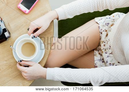 Woman's hands wearing white sweater, naked legs, black manicure, mobile phone, camera and cup of coffee on light wooden table, flat lay, point of view.