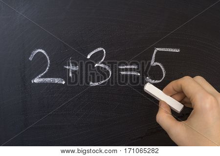 Teacher Is Writing Simple Math Equation On Blackboard With Chalk