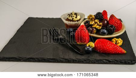 set of various nuts and fruit with chocolate muffin with a white cream energetic and tasty set