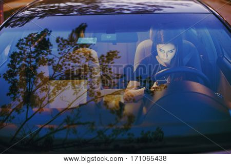 beautiful girl model sitting in the car and use the phone