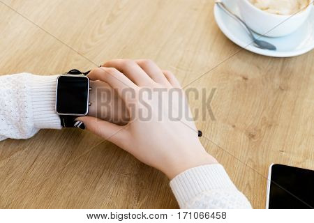 Woman's hands wearing white sweater and smart watch on hand, mobile phone, cup of coffee on light wooden table, mock up, close up.