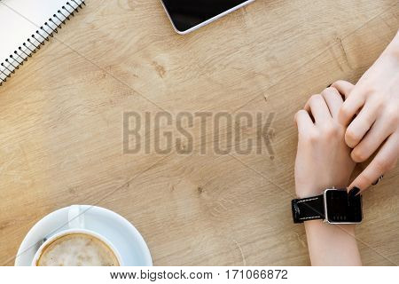 Woman's hands with black manicure touching smart watch on hand, mobile phone, cup of coffee and notebook on light wooden table, mock up, close up, copy space.