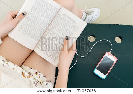 Woman's hands with black manicure holding opened book, mobile phone with headphones on bench, flat lay, mock up, point of view, copy space.