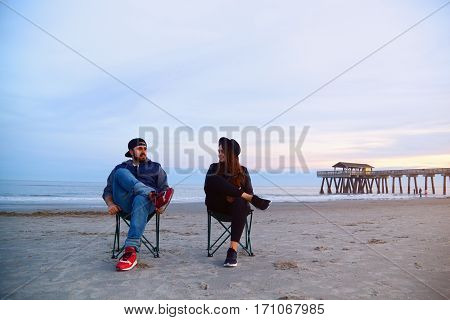 Couple Sitting In Deck Chairs At Beautiful Sunset Beach