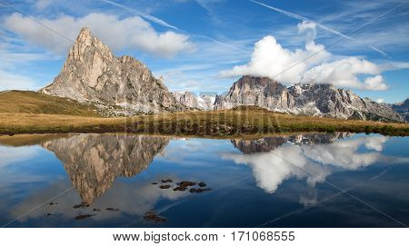 View from passo Giau to mount Ra Gusela from Nuvolau gruppe and Tofana or Le Tofane Gruppe with clouds mountain mirroring in lake Dolomites Italy