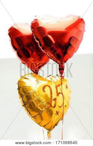 Celebrating 25th years anniversary golden label with ribbon and balloons