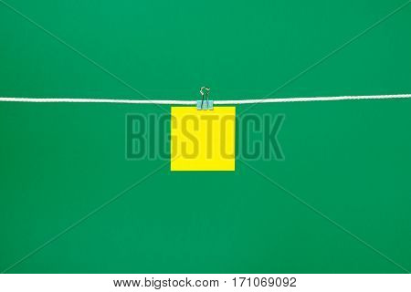 Blank yellow paper sheet on the string over green background