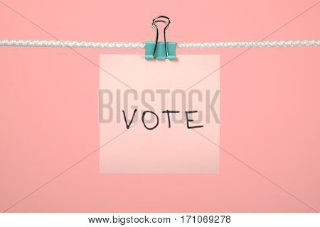 """Pink Paper Note On Clothesline With Text """"vote"""""""