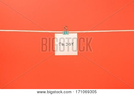 """Pink Paper Note On Clothesline With Text """"enjoy"""""""