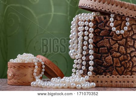 birch bark boxes with pearl beads on green fabric background