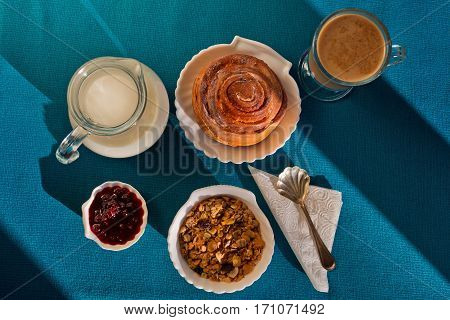 This delicious breakfast made in shell-like crockery consists of muesli, cinnamon roll. ja, and cappuchino coffee