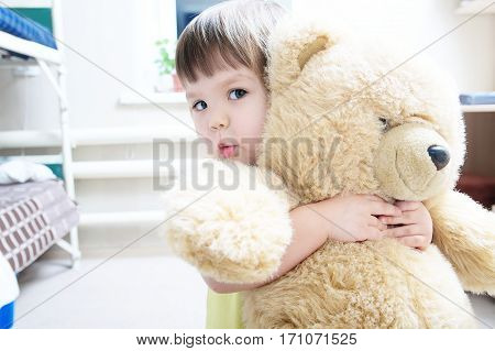 child hugging teddy bear indoor in her room devotion concept big bear toy
