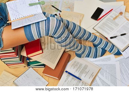 Teenage girl studying in college or school is preparing for her exams in rush, sitting the books stack