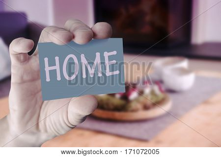 hand holding card with the word Home in front of living room