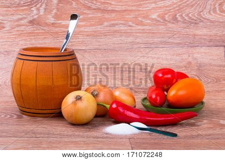 collection of fresh raw vegetables and small barrel with spoon on wooden background
