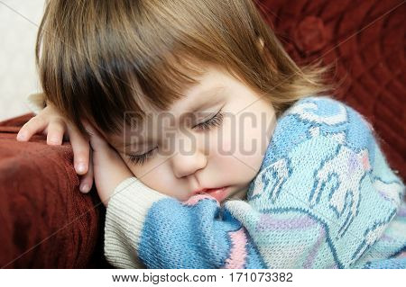 Tired child sleeping portrait on chair closeup exhausted kid fall asleep after playing