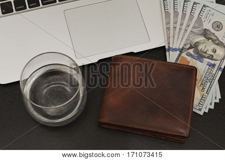 Laptop, leather wallet and some US dollars on the table - everything is ready for purchases