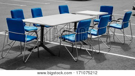Office concept. The table and chairs for office negotiations stand on the street in the parking. The photo black-and-white seats and backs of chairs are allocated in blue color.
