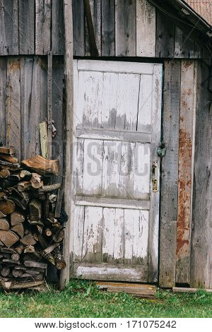 The door of the old barn with peeling off white paint. Near lay the stacked wood in a pile. Door closed on the lock.