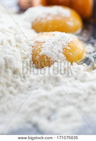 raw egg yolk in flour shot with selective focus to gain copy space at the base of this vertical image
