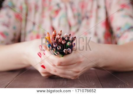 pencil bunch in woman hands on table