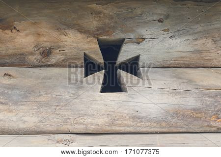 Slit in the form of a cross in a wooden frame. Backgrounds and textures