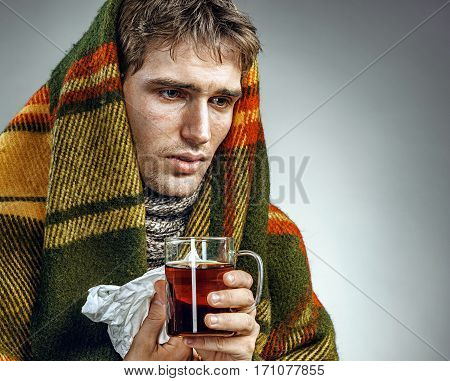 Ill Man covered with plaid blanket with hot tea. Sick man suffering cold and winter flu virus. Health care concept