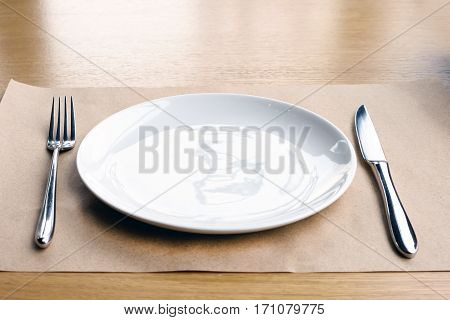 Empty white plate, fork and knife, on a wooden table in a restaurant