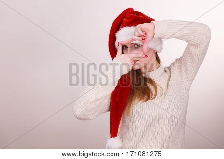 Christmas girl making finger frame gesture. Young lady wearing santa cap. Celebration holiday relax fashion concept.