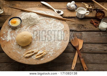 Prepared dough on wooden table with flour and egg. Cooking at home best recipe for baking bread and pastry.