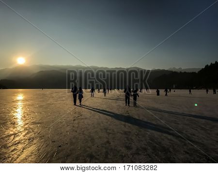 sunset over frozen lake Bled people walking