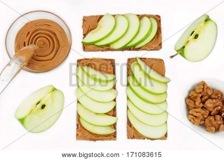 Sandwiches with peanut butter and an apple on the table close-up. Apple slices walnuts isolated on white background. Horizontal top view.