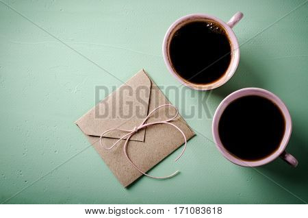 Love letter, envelope and two pink cups of coffee. Valentines card. Horizontal, flat lay, top view