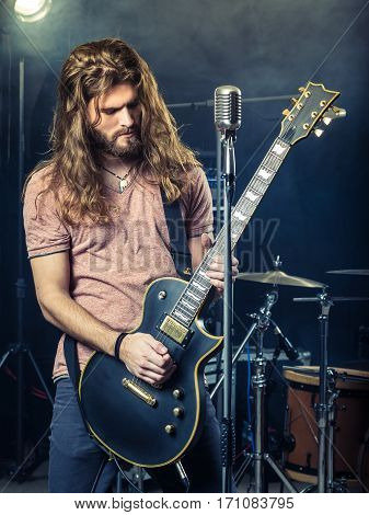 Photo of a young man with long hair and beard playing electric guitar on stage.