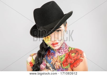 Pretty girl with dark long hair wearing black hat, body art paintings on neck, shoulders and face, painting flowers, make up model, closed eyes, copy space.