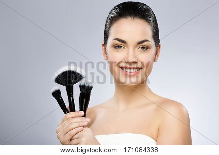 Darkhaired  girl with black fixed hair behind, dark big eyes and naked shoulders wearing bath robe and looking at camera, holding make-up brushes, smiling.