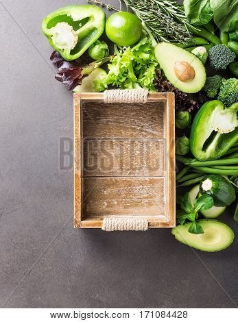 Background with assorted green vegetables, salad, avocado, bell pepper and Brussels sprouts with wooden tray on light brown stone table top. Healthy food concept with copy space.