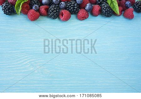 Various fresh summer berries on wooden background. Ripe blueberry raspberry with basil leaves. Berries at border of image with copy space for text. Top view.