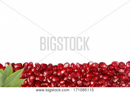 Background made of red pomegranate seeds. The scattered red grains of a pomegranate on a white background. Garnet at border of image with copy space for text. Top view.
