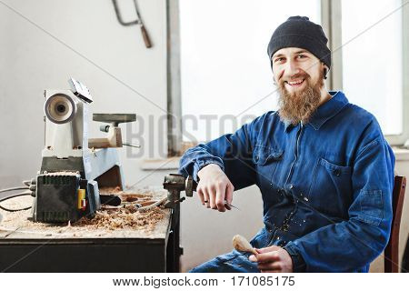 Man with a beard wearing blue jeans suit and black hat sitting on working place, woodcarving instruments on table, big window at background, smiling.